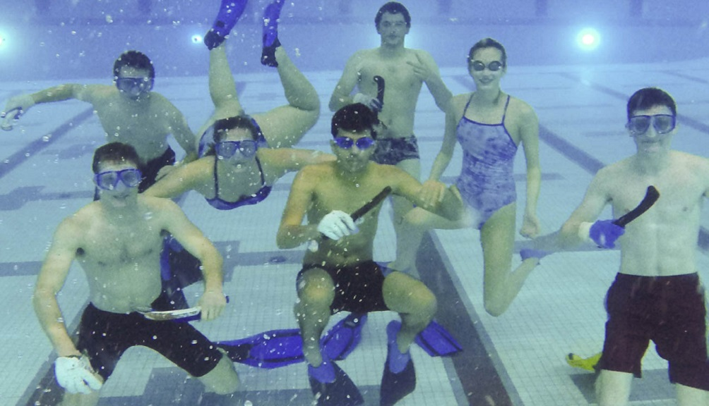 Seven students are underwater with snorkels, goggles, and their underwater hockey equipment, smiling at the camera.