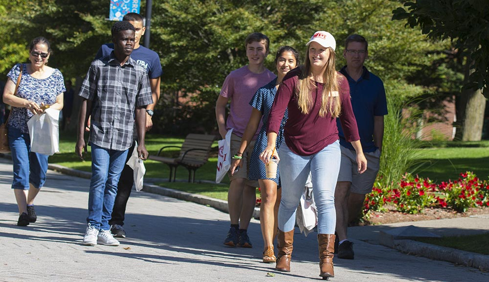 A student tour guide leads prospective students and their families along a stone path through the heart of campus.