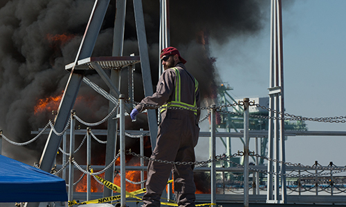 Worker in a fire suit watching over a controlled oil burn