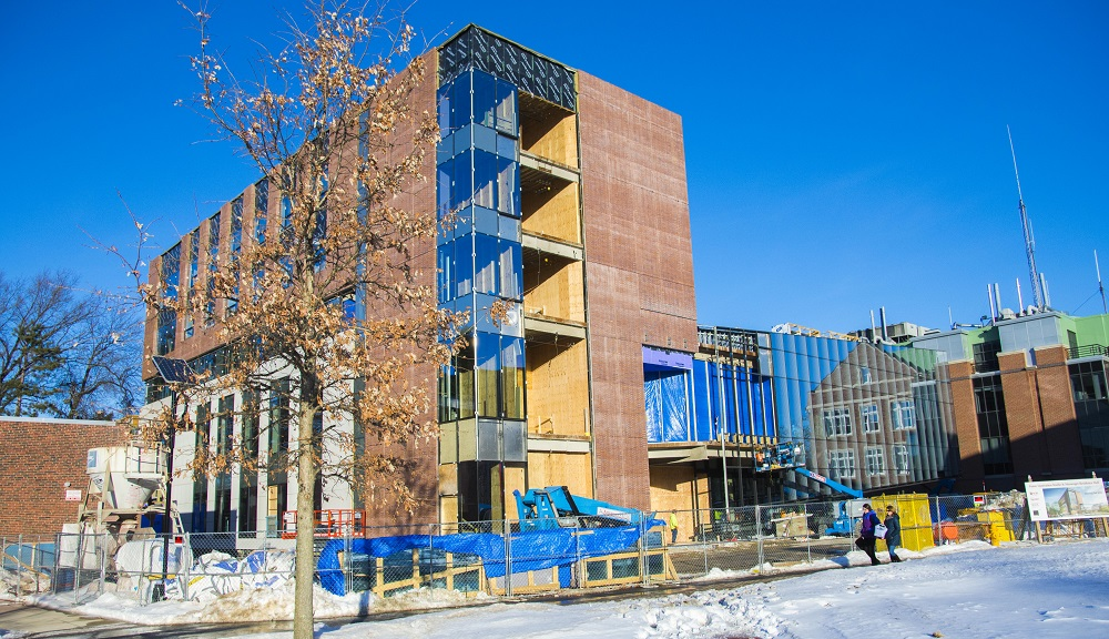 A shot of the Foisie Innovation Studio & Messenger Residence Hall under construction, with a blue sky behind it.
