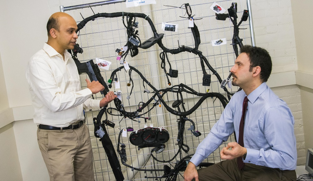 Alex Wyglinski and Raghvendra Cowlagi discuss the technology involved in autonomous vehicles, with a wiring harness for a 2014 Chevy Impala in the background.