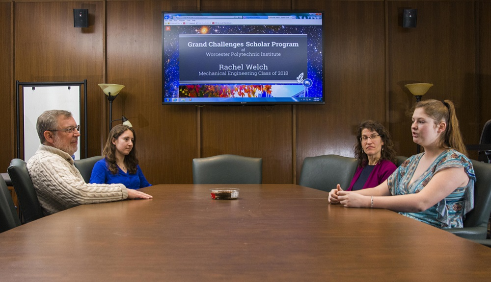 Two faculty members sit across a conference table from two students, with a computer screen projected in between them that reads,