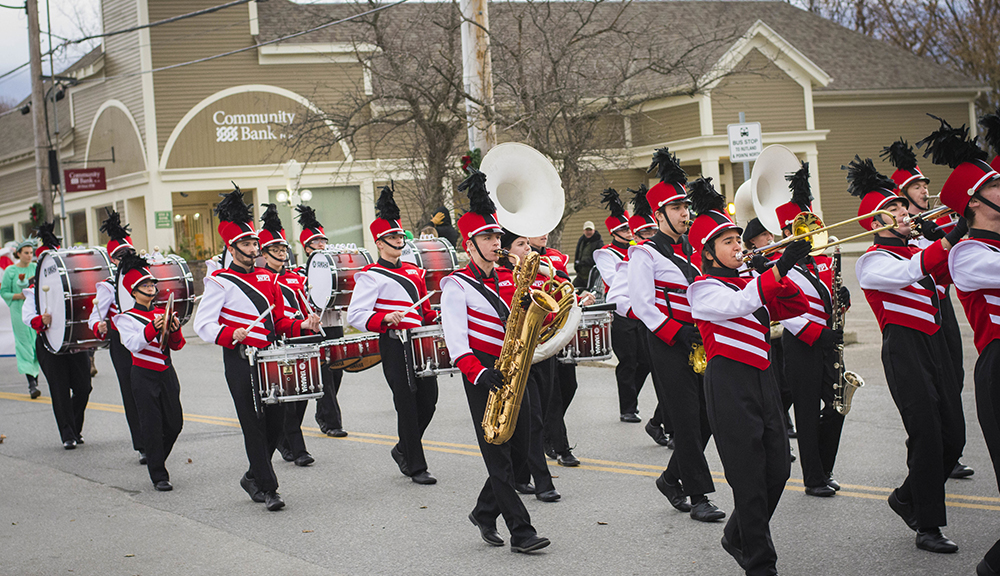 The WPI Pep Band marches down Main Street in Manchester, Vermont, wearing their black, red, and white uniforms and playing a variety of instruments.