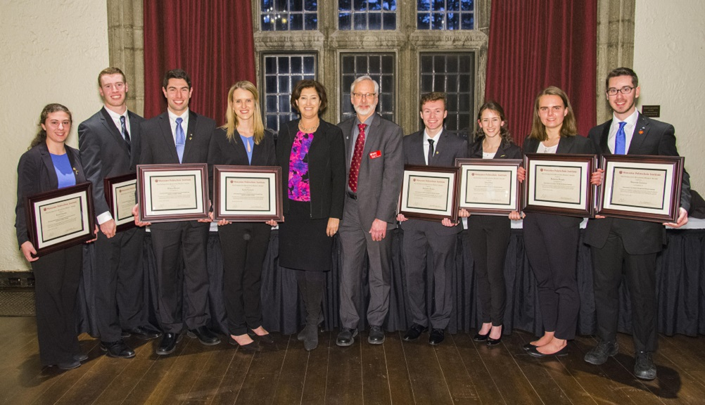 Two teams of four students each stand on either side of President Leshin and Kent Rismiller. All are dressed in professional attire, the students are holding framed certificates, and there are large windows with red curtains in the background.