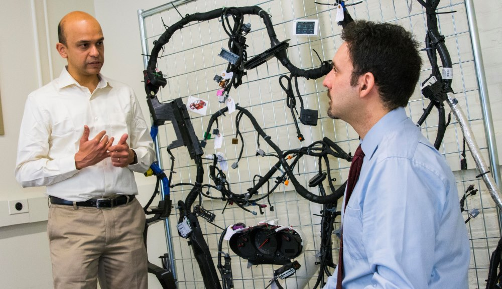 Raghvendra Cowlagi, left, and Alexander Wyglinski, in the MITRE-WPI Collaboratory. Behind them is the wiring harness for a 2014 Chevy Impala, used for projects on autonomous vehicle security.