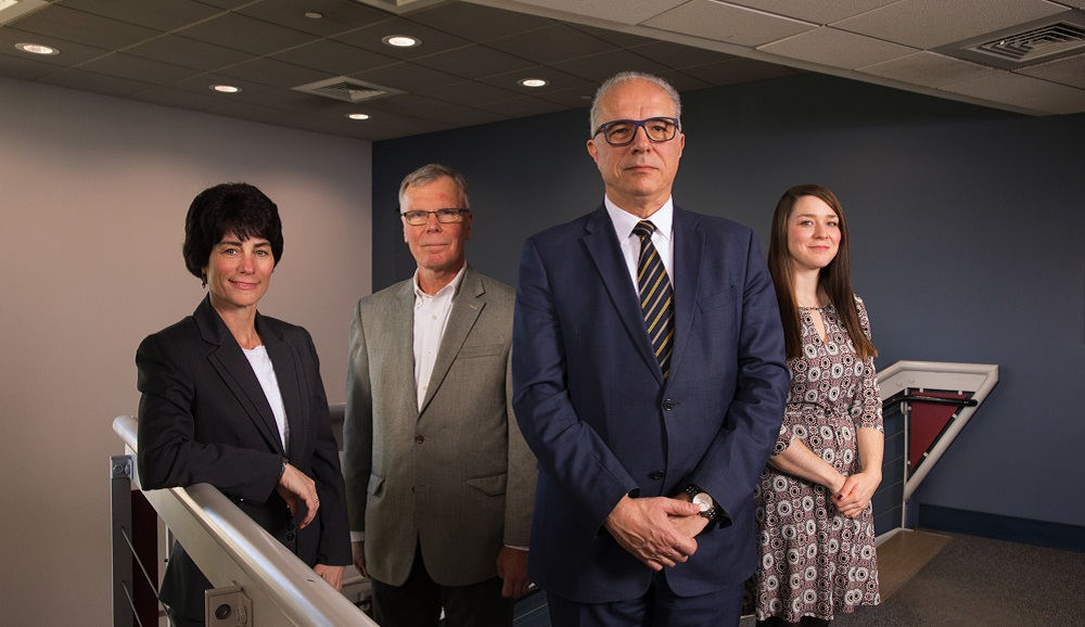 Ellen Piccioli, Michael Wright, Bogdan Vernescu, and Colleen McShea stand together at the top of a stairwell with a blue wall and gray wall behind them.