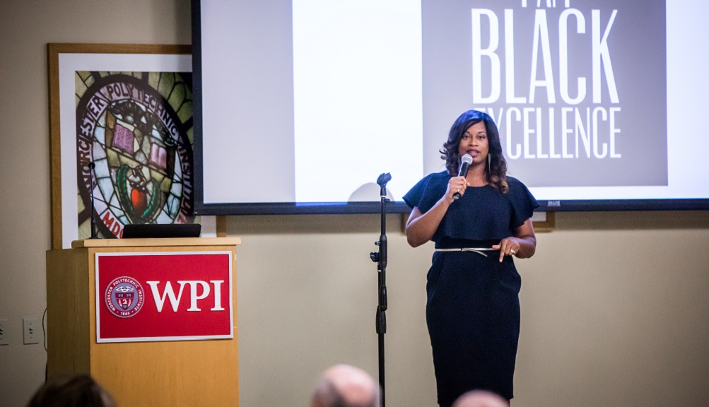 Whitney Gaskins stands near a WPI podium with a microphone in hand, addressing the audience. A projection screen reading