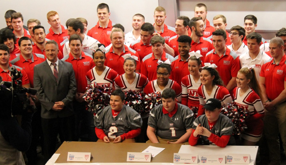 Keegan Concannon sits at a table with two friends, while the WPI football team and cheerleaders are gathered around him.