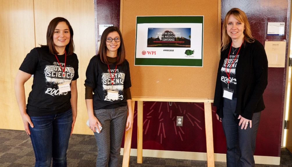 Three female Women in Data Science volunteers in matching T-shirts stand next to the official conference sign. They're all smiling and wearing lanyards, and one is wearing glasses.