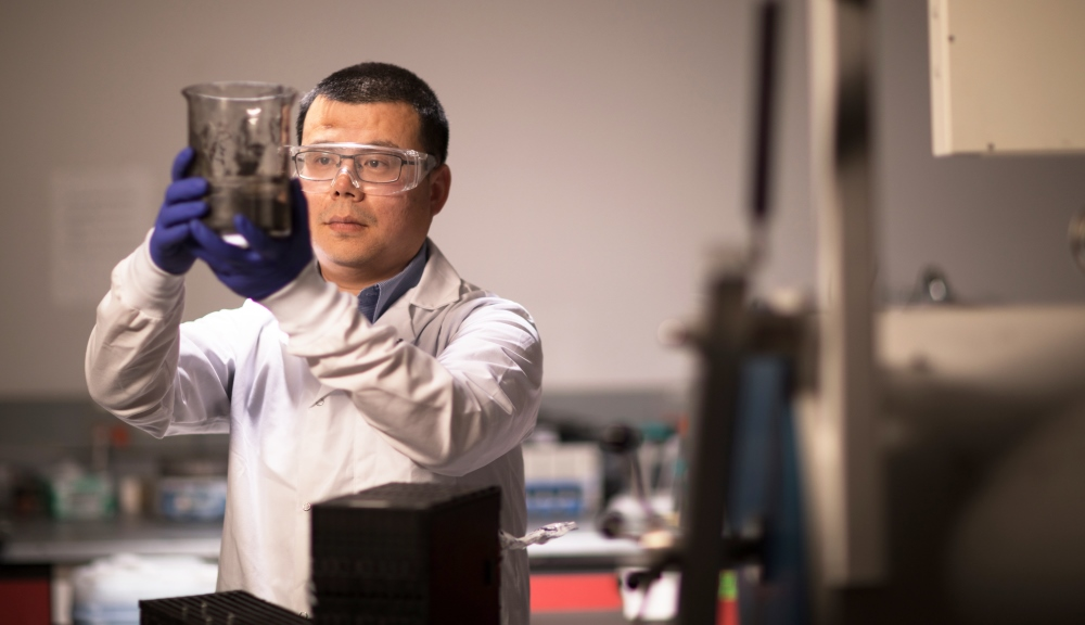 Yan Wang, dressed in a lab coat, holds up and looks at a large beaker containing a black material