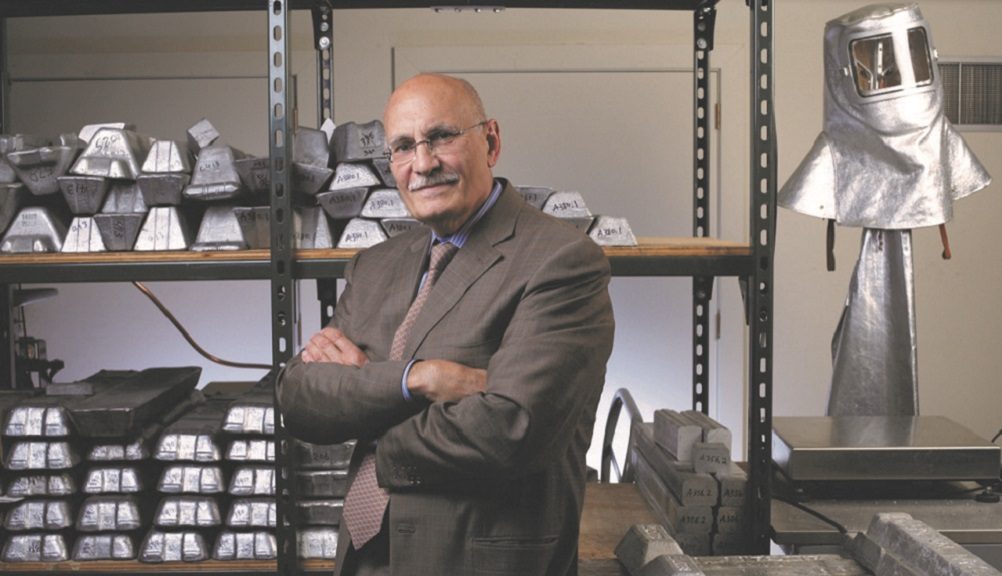 Diran Apelian stands in front of several shelves holding multiple pieces of metal. There's also a silver safety helmet behind him. He's got his arms crossed in front of him, and is wearing glasses and a dark suit and tie.