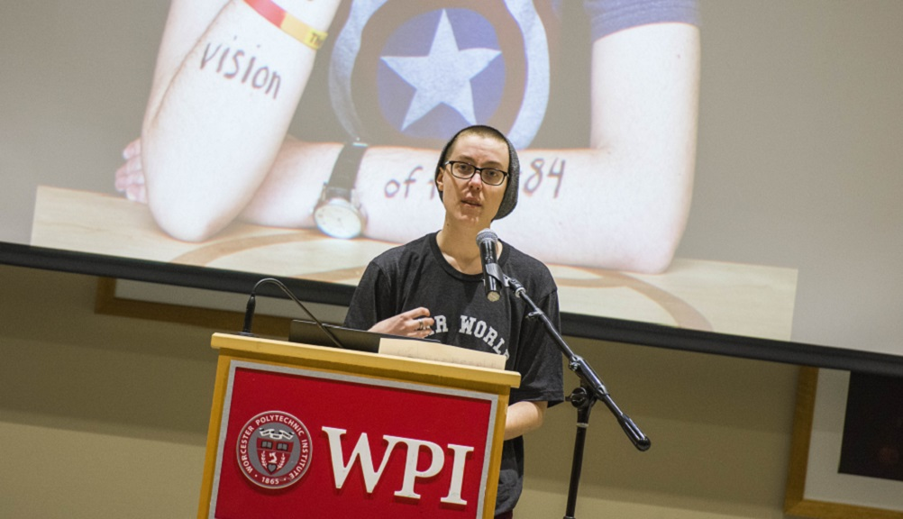 A WPI student stands at a podium as their Dear World portrait is displayed behind them, holding a piece of paper and sharing their story with the crowd.