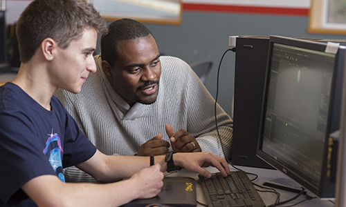 Photo of Farley Chery at WPI IMGD lab with student.