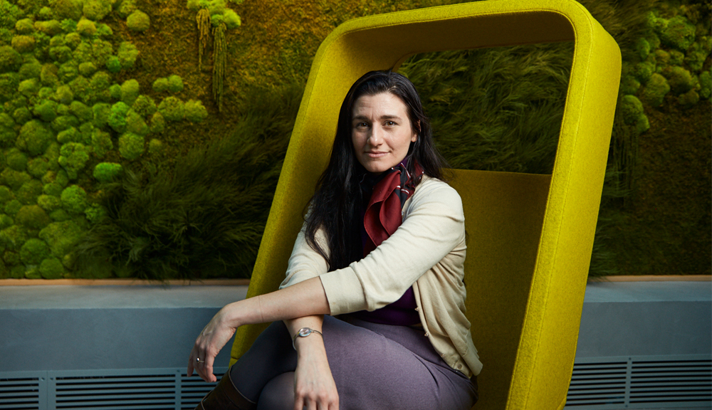 Portrait of Jenna Balestrini sitting in a yellow felted chair.