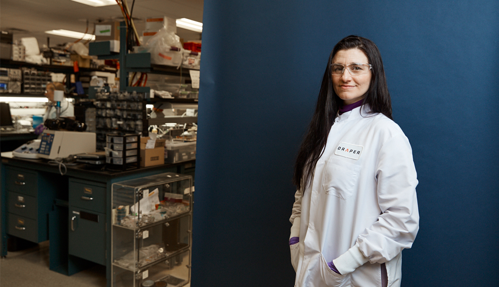 Portrait of Jenna Balestrini in full lab attire against a blue backdrop with the lab in the background.