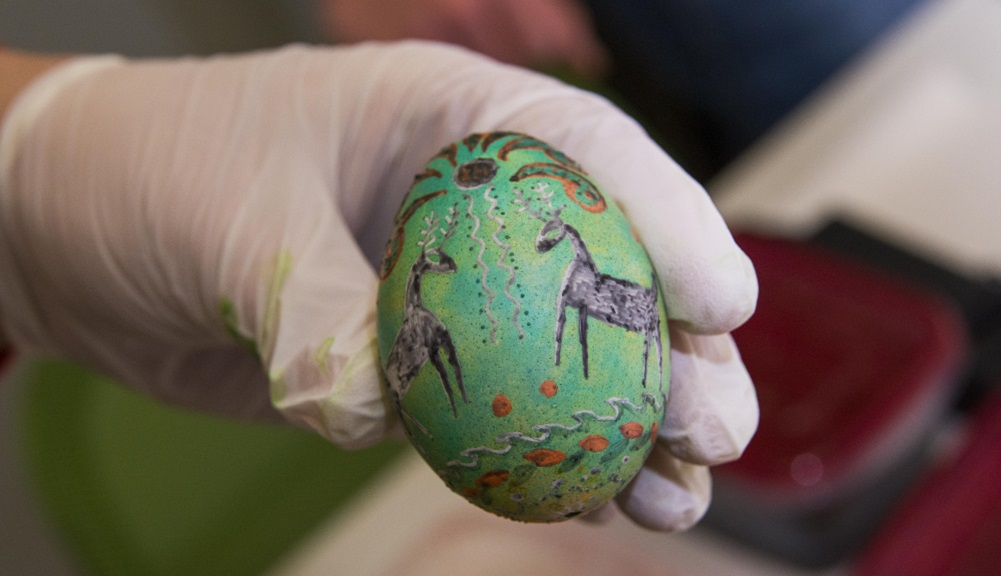 A hand covered by a white rubber glove holds up a pysanky, a green painted egg with colorful figures painted on it.