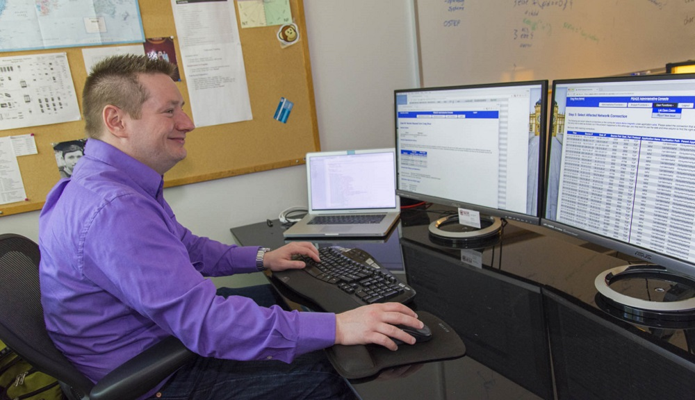 Craig Shue sits at a desk in front of three computer monitors. He's typing with one hand and mousing with the other. He's smiling, and is wearing a dark purple shirt, jeans, and silver watch.