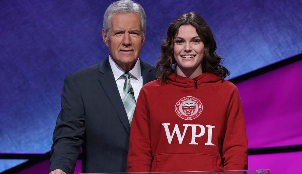 Alex Trebek (left) is wearing a suit and standing next to Alli Ross, who is wearing a red WPI sweatshirt, on the Jeopardy! set. Both are smiling.