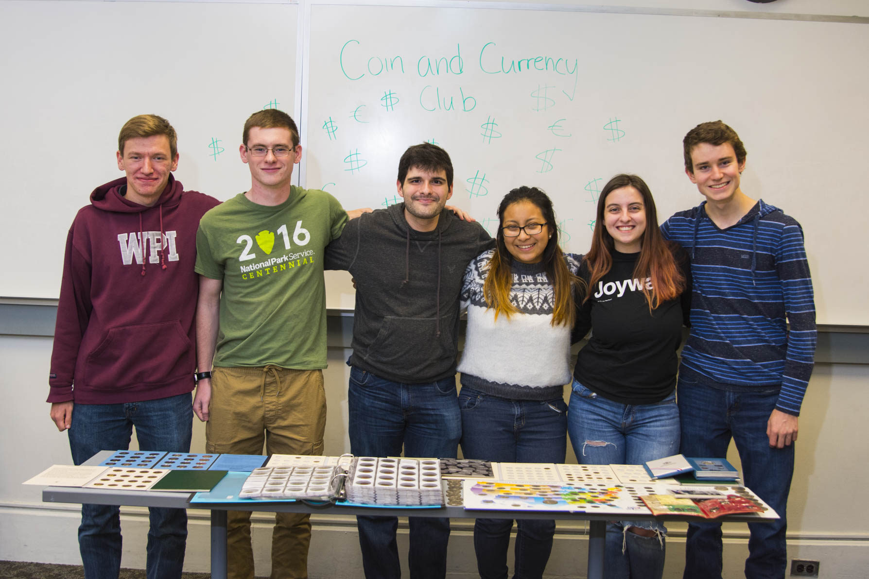 Members of the Coin & Currency Club gather in front of a table covered in binders full of coins. Their club name is written on the whiteboard behind them.