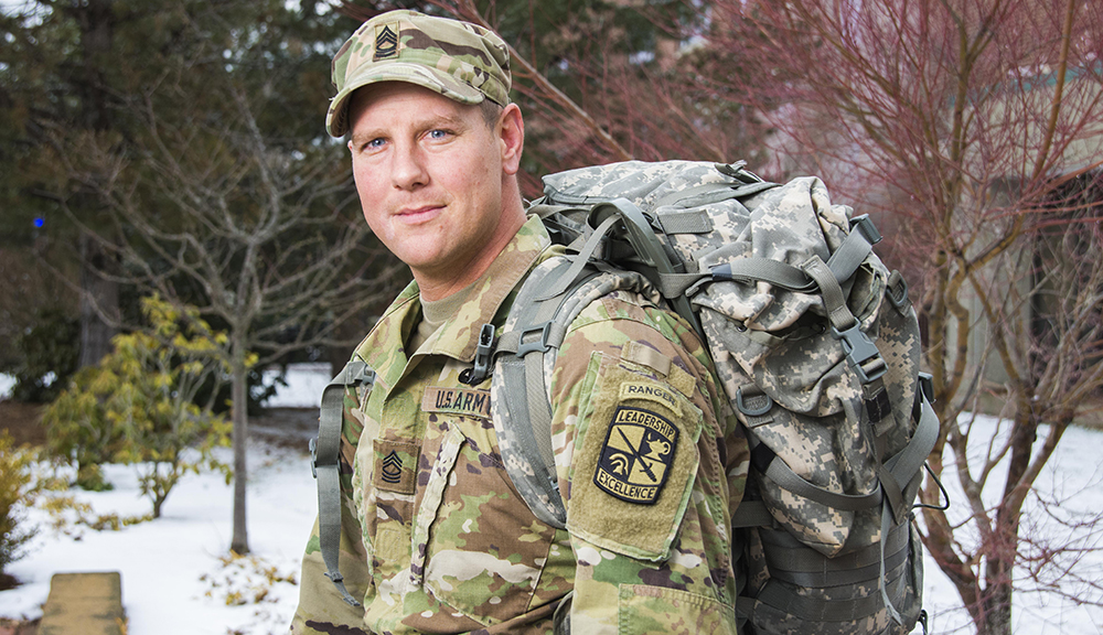 MSG Blair stands in front of several trees wearing his military uniform and carrying his ruck on his back.