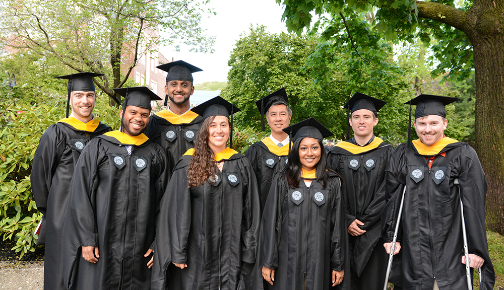 A group of graduate students take a photo together in their graduation robes following Commencement.