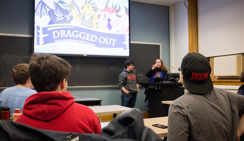 "Students gather in a classroom to discuss a game, ""Dragged Out,"" which is projected on screen while two students stand at a podium in mid-discussion."