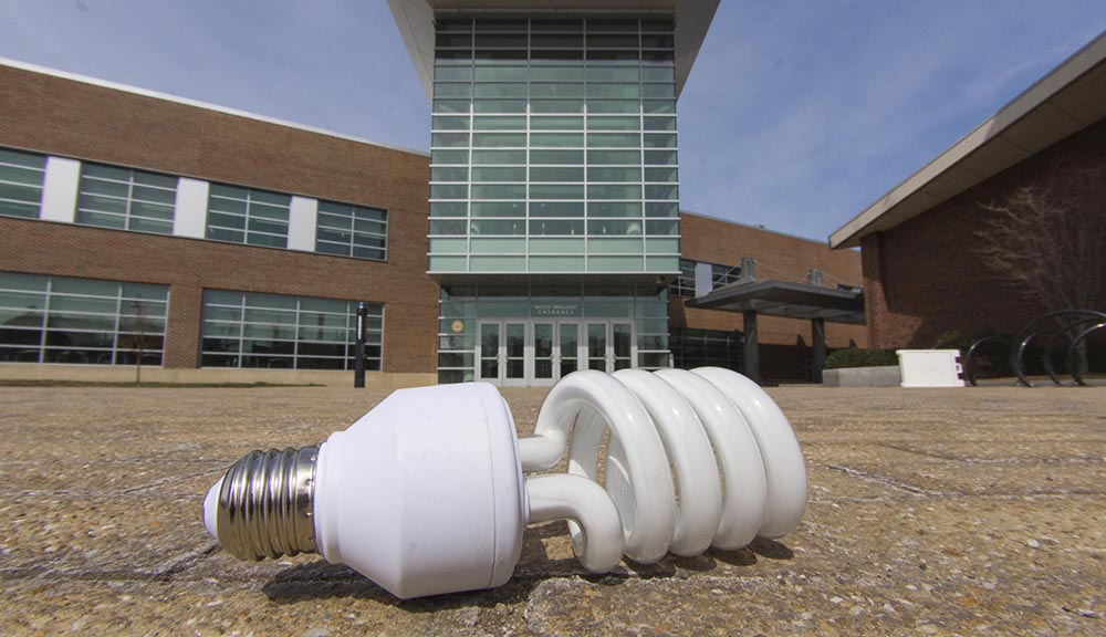 A photo of an energy-saving lightbulb on the ground in front of the Sports & Recreation Center.