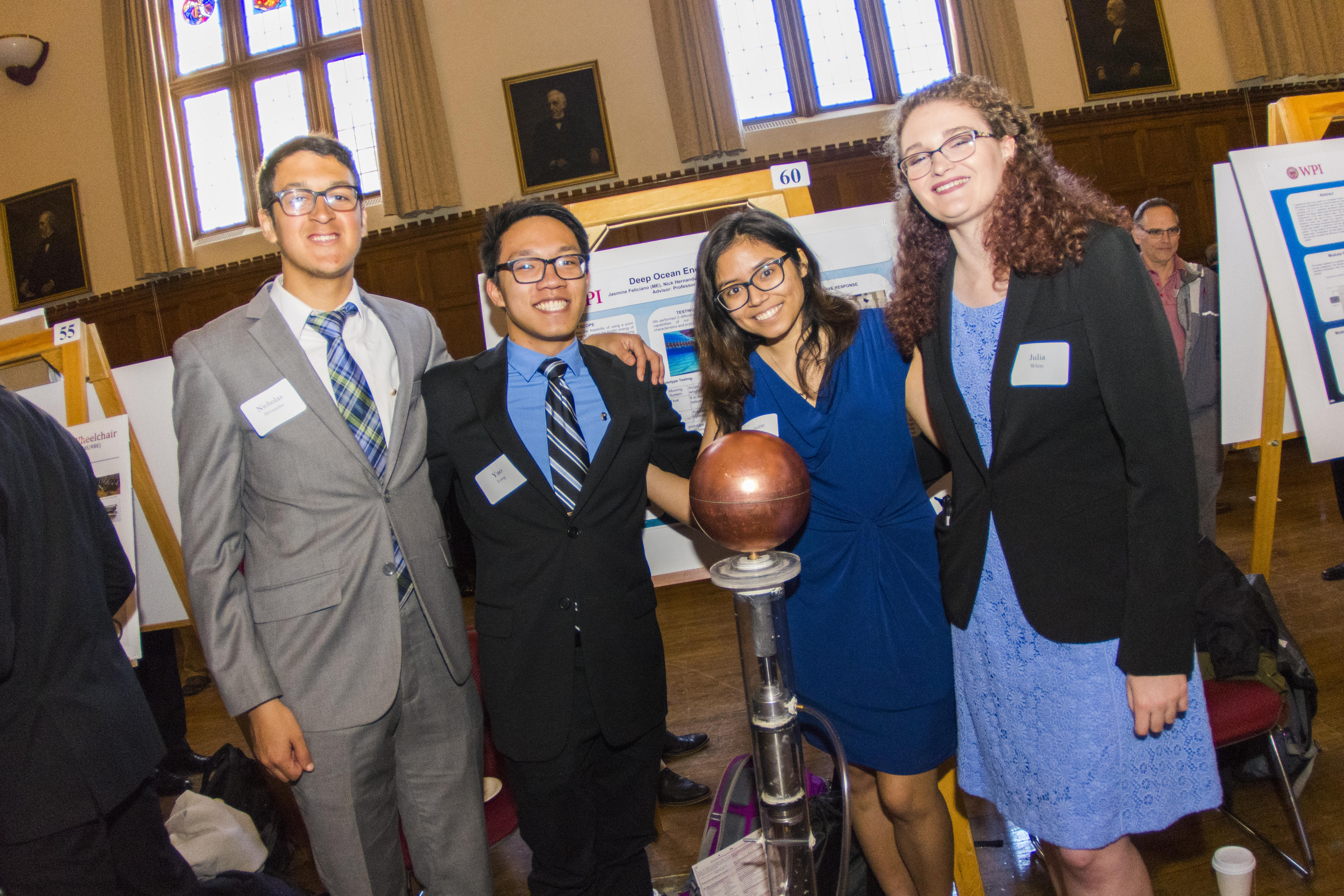 Four students stand in front of their MQP, a deep ocean energy harvester. They're dressed in business outfits, and are all smiling.
