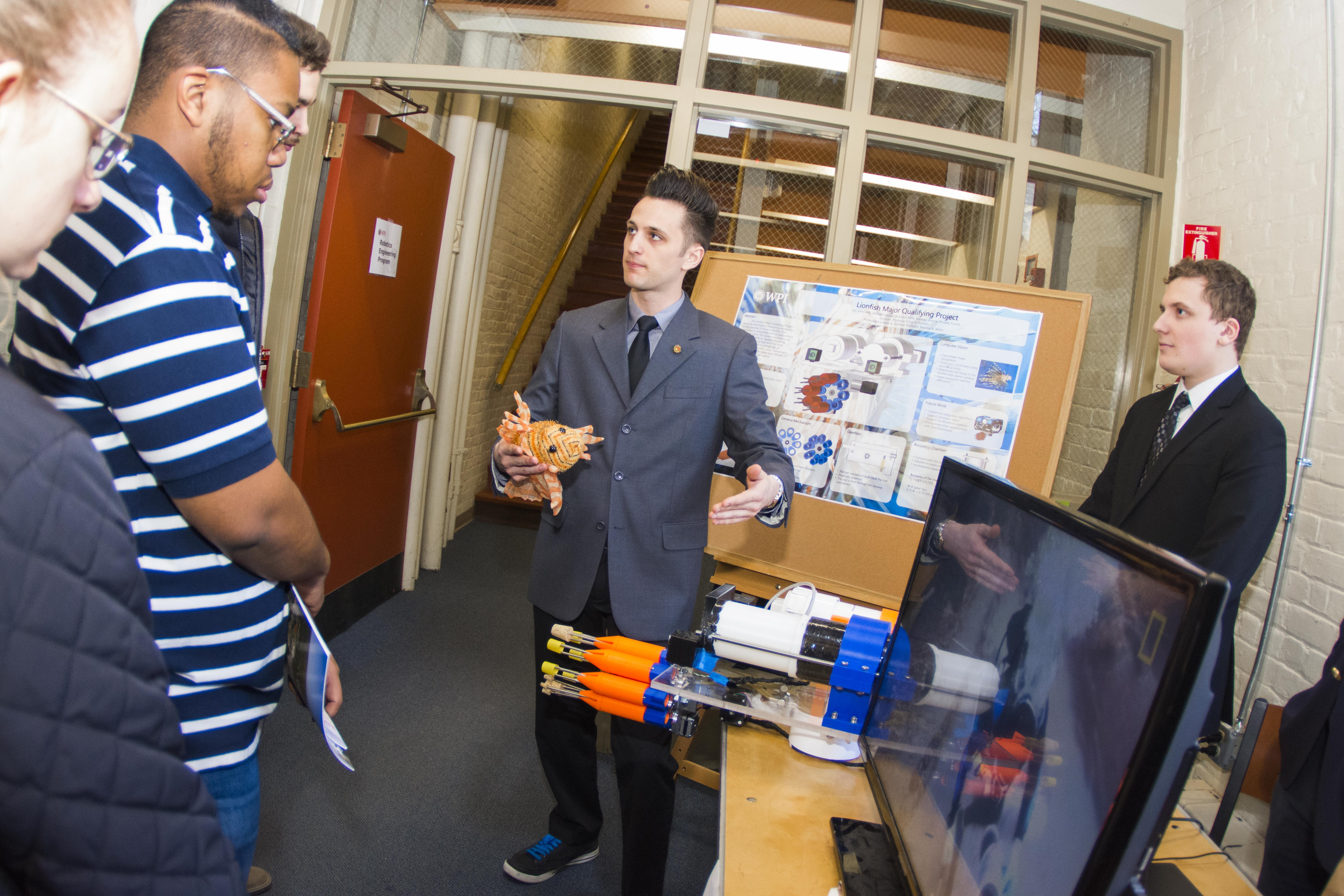 A student explains his team's MQP, a harvester to catch lion fish.