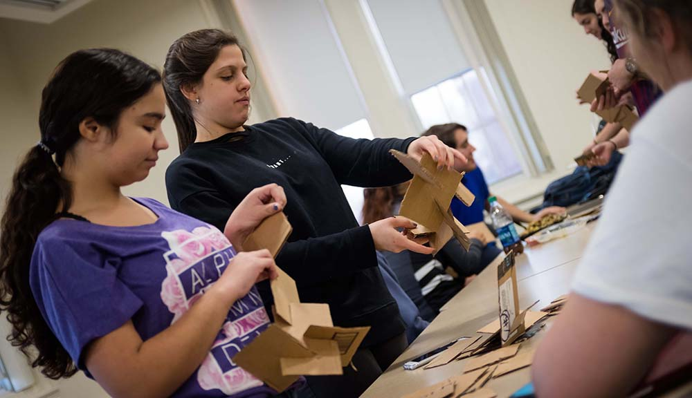 Two students hold pieces of cardboard and work to connect them together as part of an engineering project.