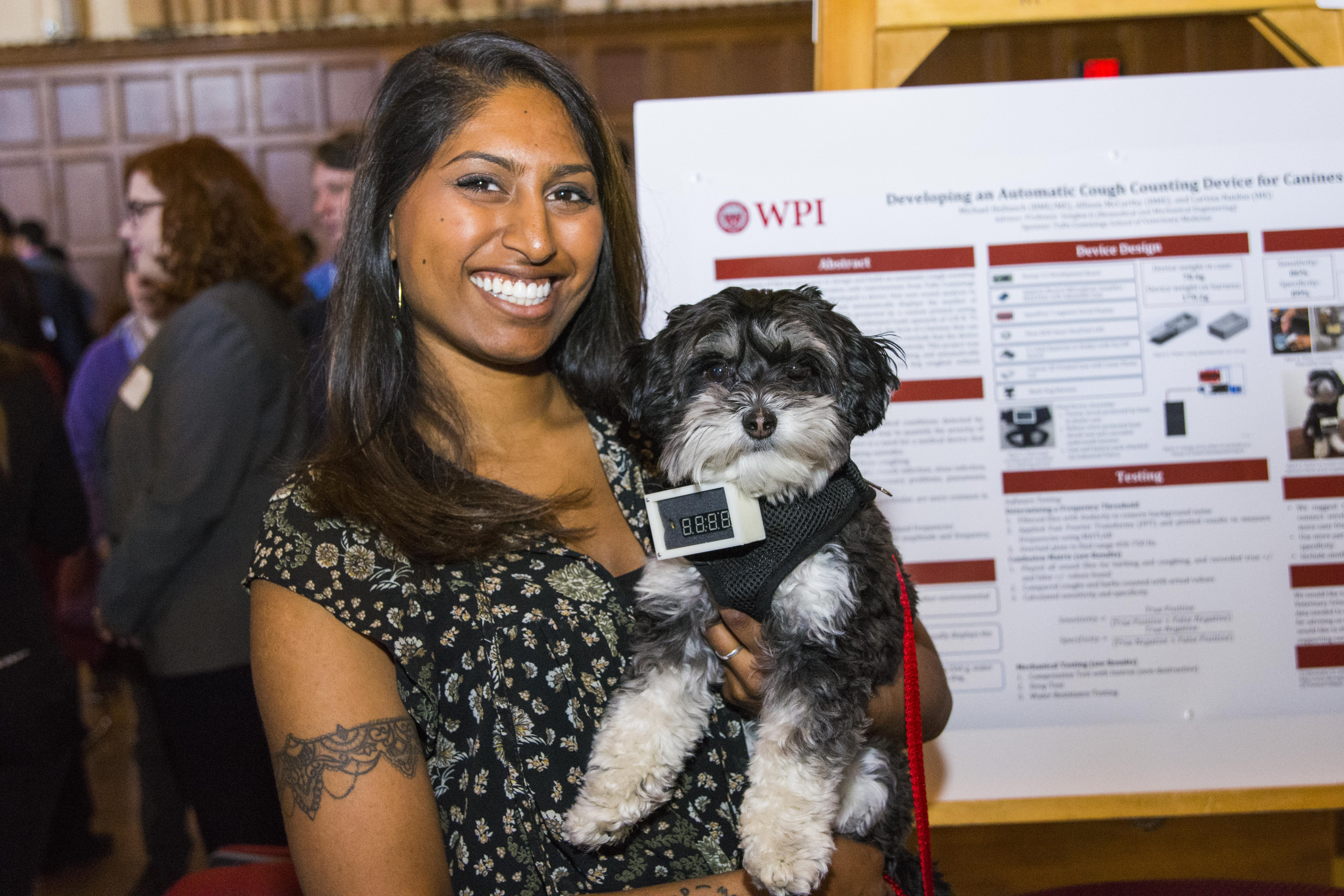 A student holds up her puppy with her team's poster work in the background. She's wearing a black patterned shirt, has a tattoo on her arm, and is smiling.