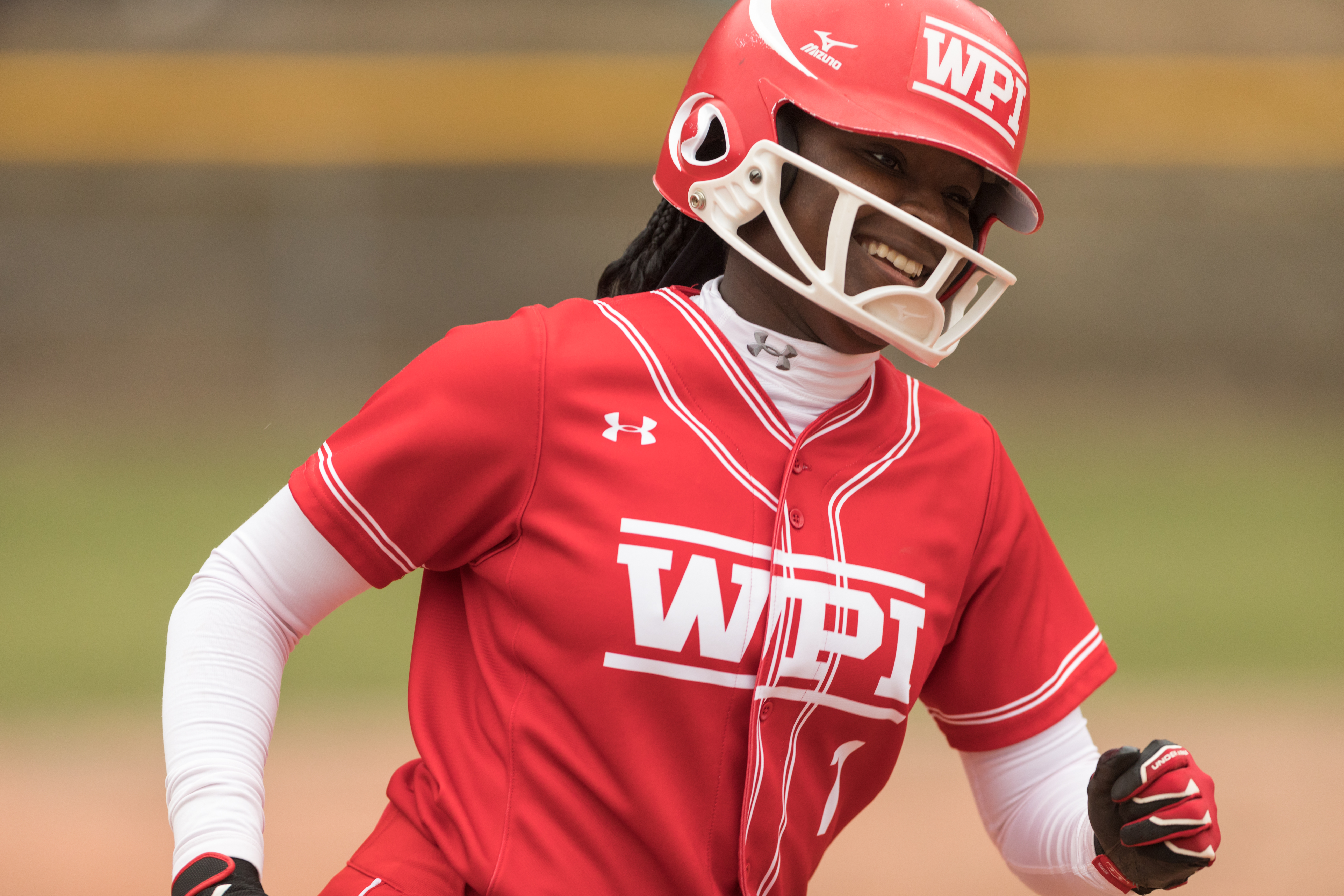"Ama Biney smiles while rounding the bases during a WPI softball game. Her helmet and jersey are red and emblazoned with ""WPI."""