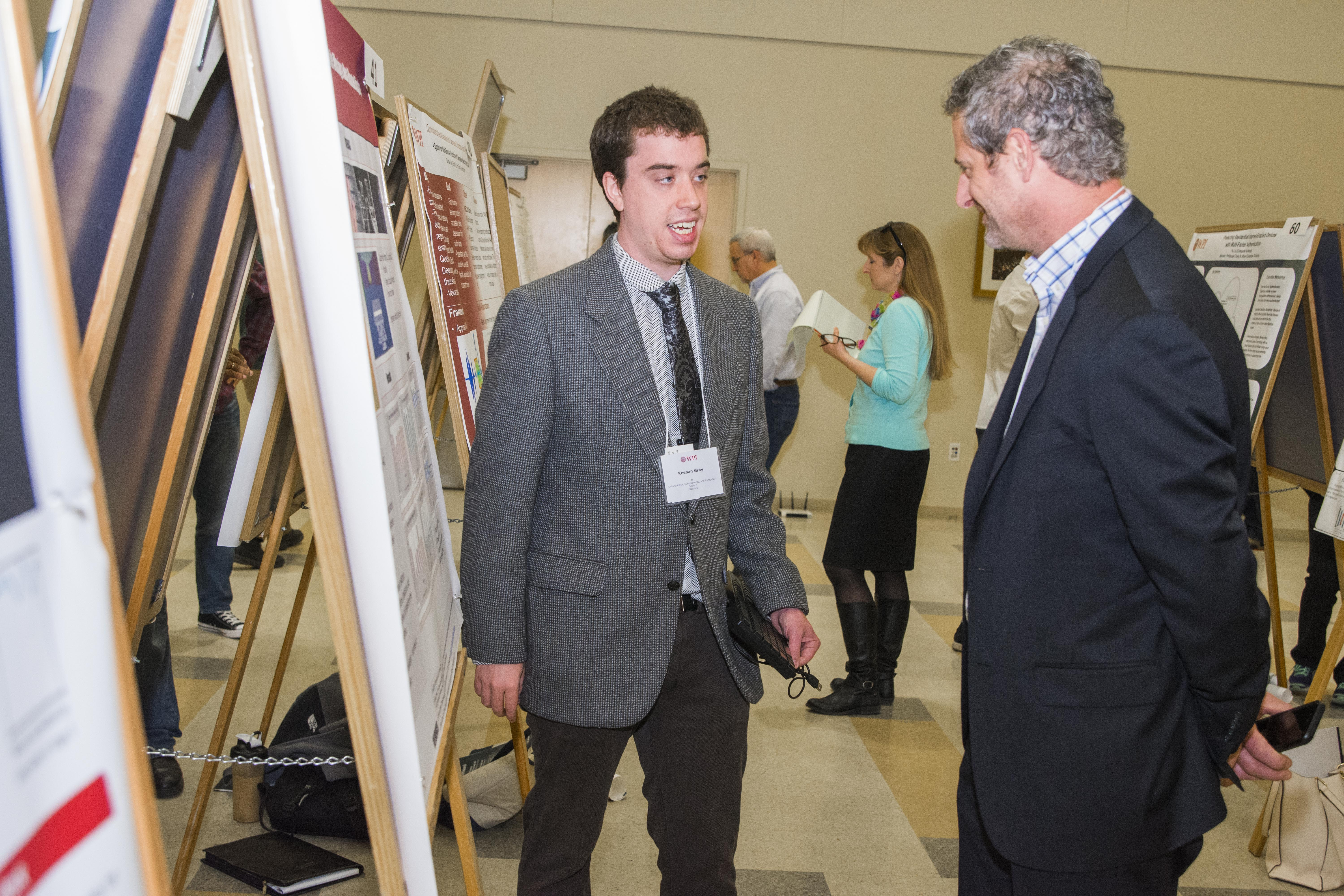 A student dressed in a suit and tie explains his project work to a judge, also in professional dress.