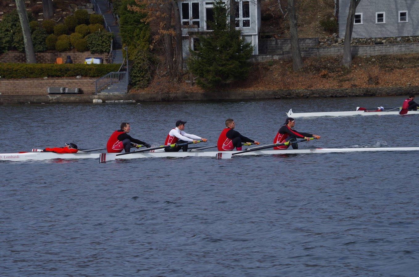 The men's rowing team practices on the lake wearing red and white gear.