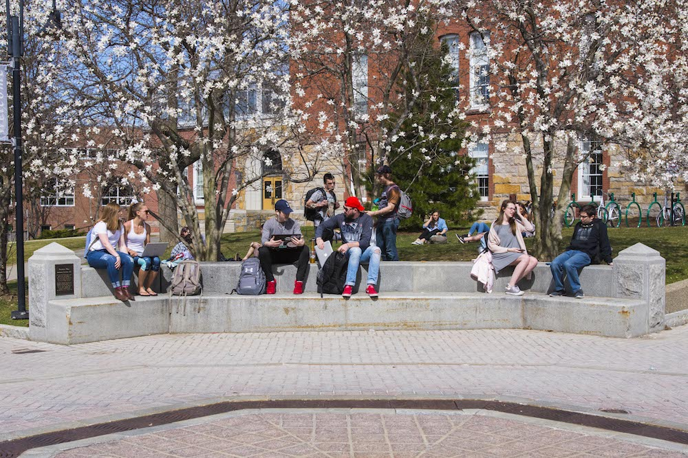 Several students sit on the concrete area around the Fountain in the center of campus as buds bloom on the trees behind them.