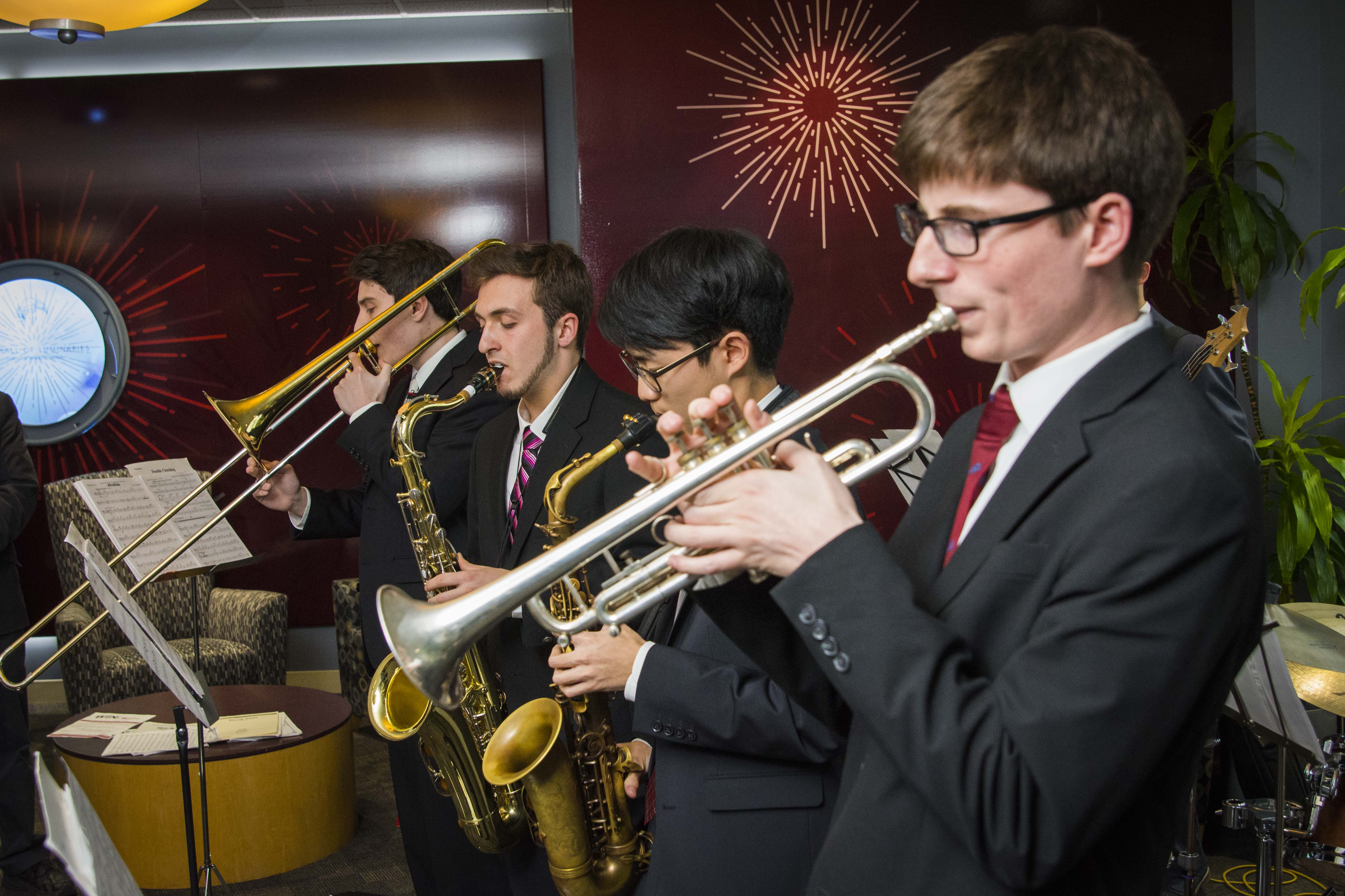 Dressed in formal attire, students play instruments during an event in the Odeum.
