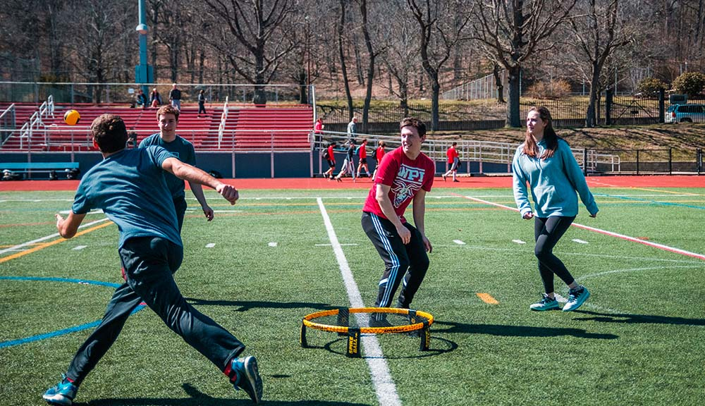 A student lunges after a spikeball as two other students look on.