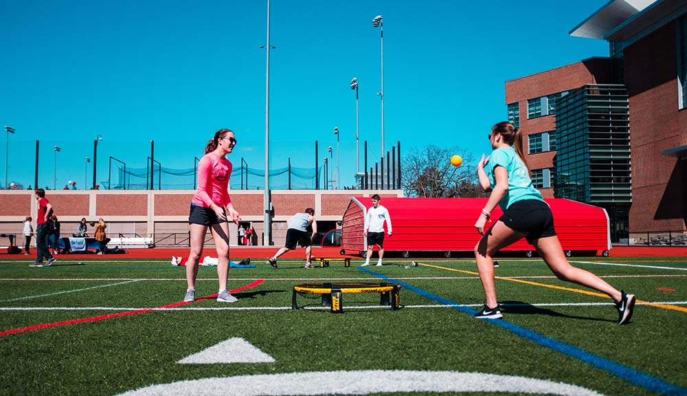 Two students practice a game of spikeball while several others gather in the background.