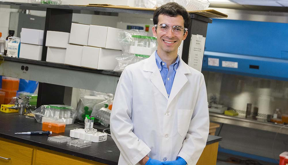 Alex Markoski stands in a lab. He's wearing safety glasses, blue rubber gloves, and a lab coat, and is smiling at the camera with his hands folded in front of him.
