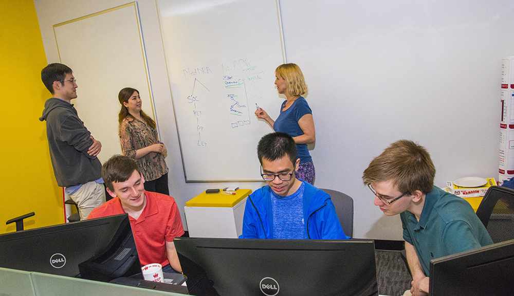 Two students stand at a white board in the background of the photo while their professor explains something to them. Three other students sit in the foreground, studying information on computers.