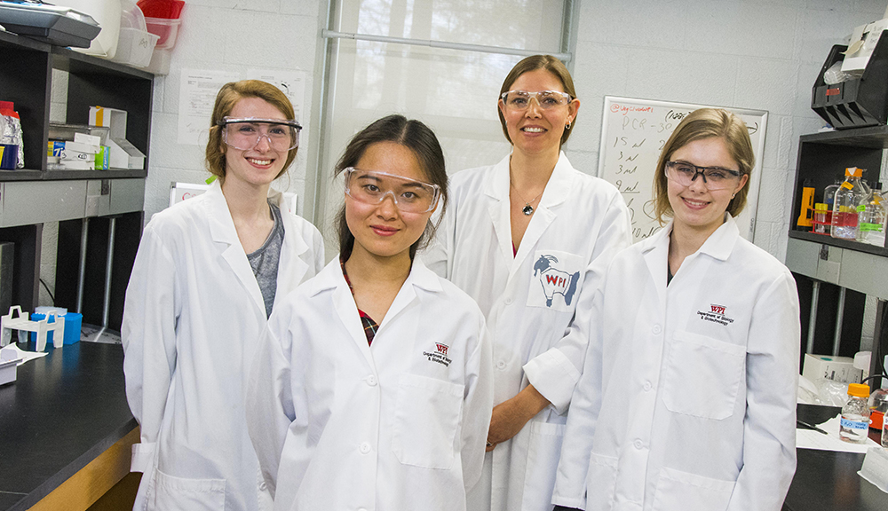 Natalie Farny (center) and her students pose in their lab, between two lab tables. They're all smiling and are wearing lab safety coats and gear.