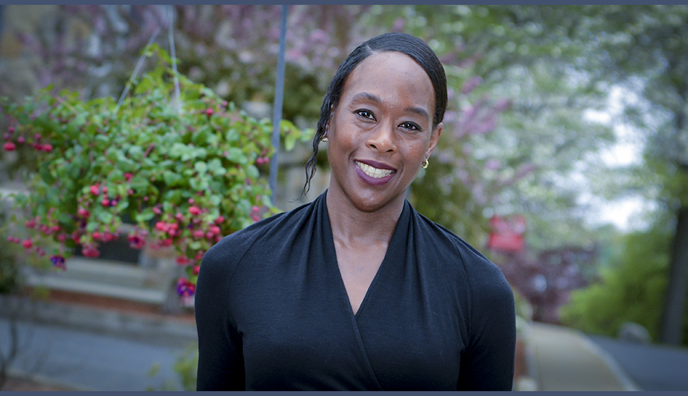 Margot Lee Shetterly smiles in front of a background of greenery and flowers. She's wearing a black shirt, and has her hair pulled back.