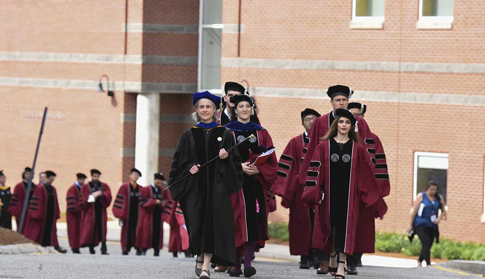 Kris Boudreau (center) wears a black robe and leads graduates and faculty throughout campus.