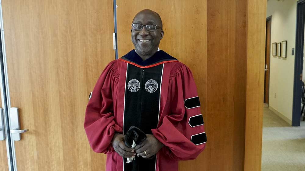 Wole Soboyejo stands in his commencement robes in front of a wooden background. He's wearing glasses and is smiling.