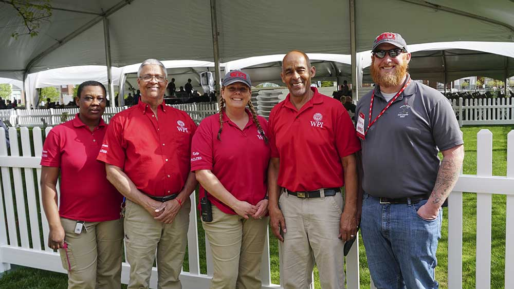 Five members of the facilities team gather at the Commencement tent on the Quad. They're all wearing WPI polos and smiling.