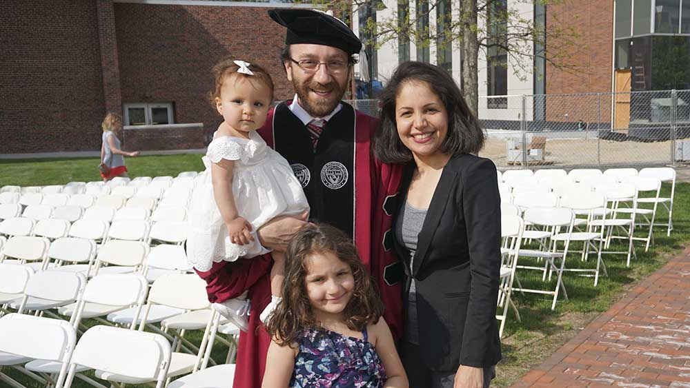 A graduate stands with his wife and daughter, while holding his youngest daughter in his arms.