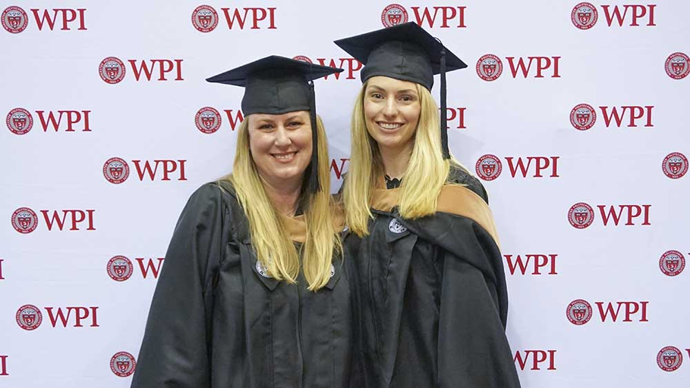 Two female students stand smiling in front of a WPI patterned background. They're both wearing their caps and gowns.