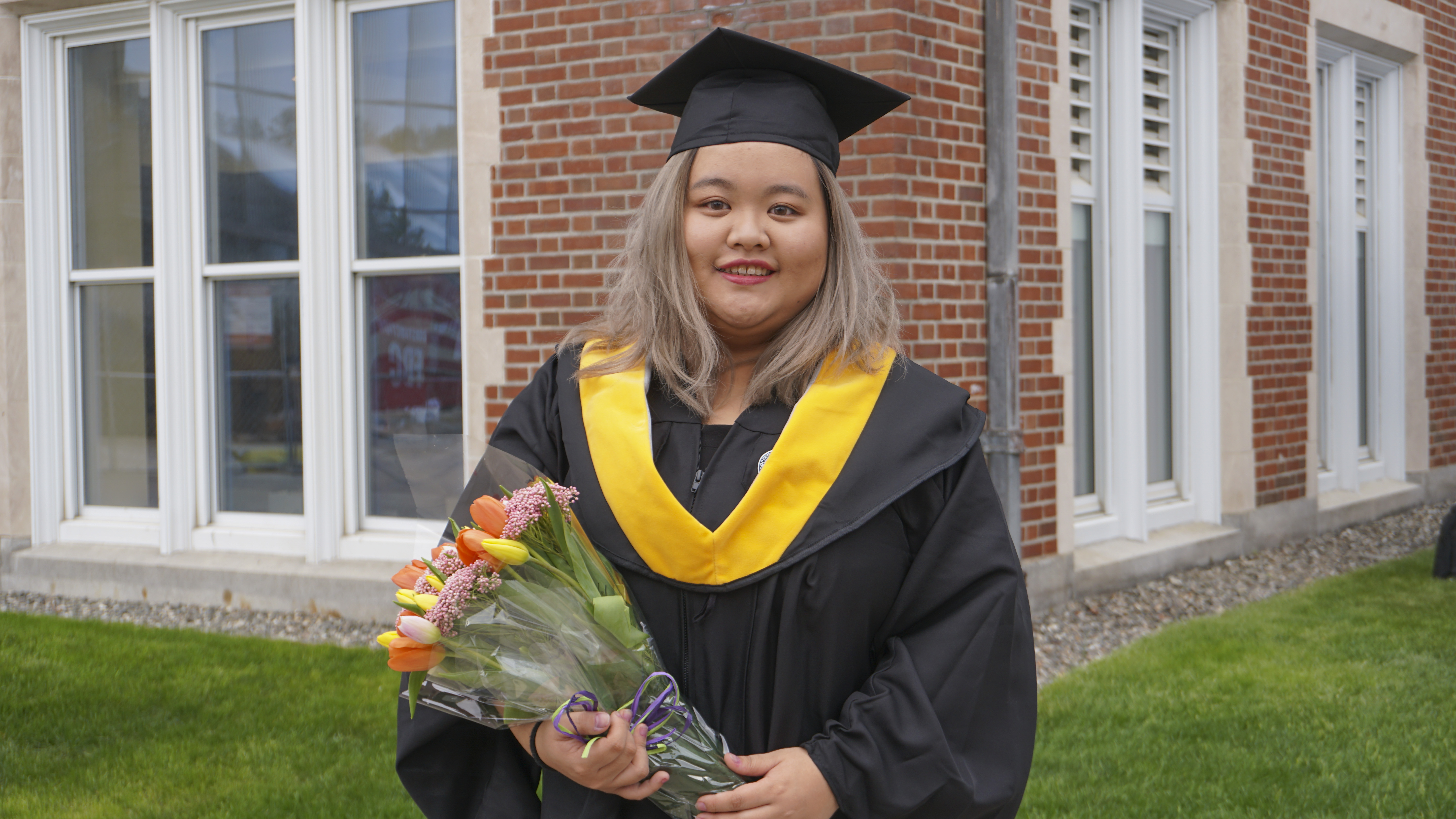 Zhenyan Lin smiles in her cap and gown while holding a bouquet of flowers.