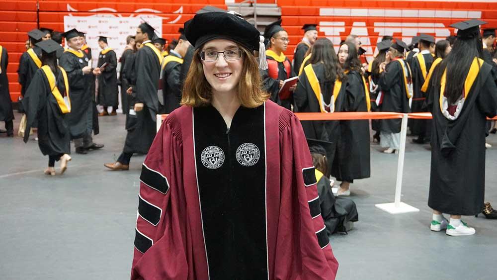 Hannah Strobel smiles in Harrington Auditorium wearing her Commencement regalia.