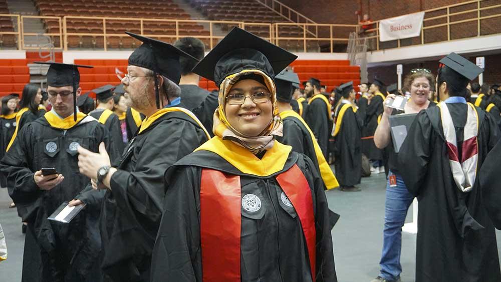 Saida Elfaquir smiles in Harrington Auditorium wearing Commencement regalia.